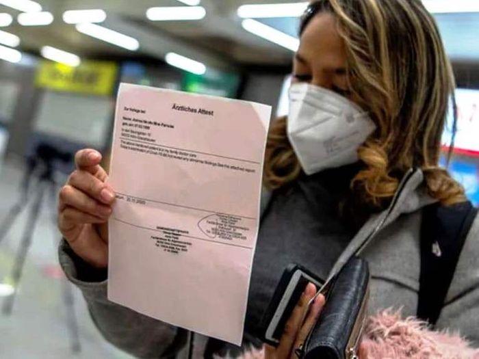 Пассажирка в аэропорту демонстрирует результат PCR теста. фото